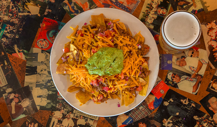 guacamole on loaded nachos aerial view at el meson de pepe